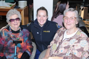 Constable Casey Wood in uniform is pictured with retired officers Mrs Judy Burgess and Mrs Margaret Medwin who are both seated at the High Tea function celebrating 100 years of women in policing with Tasmania Police.