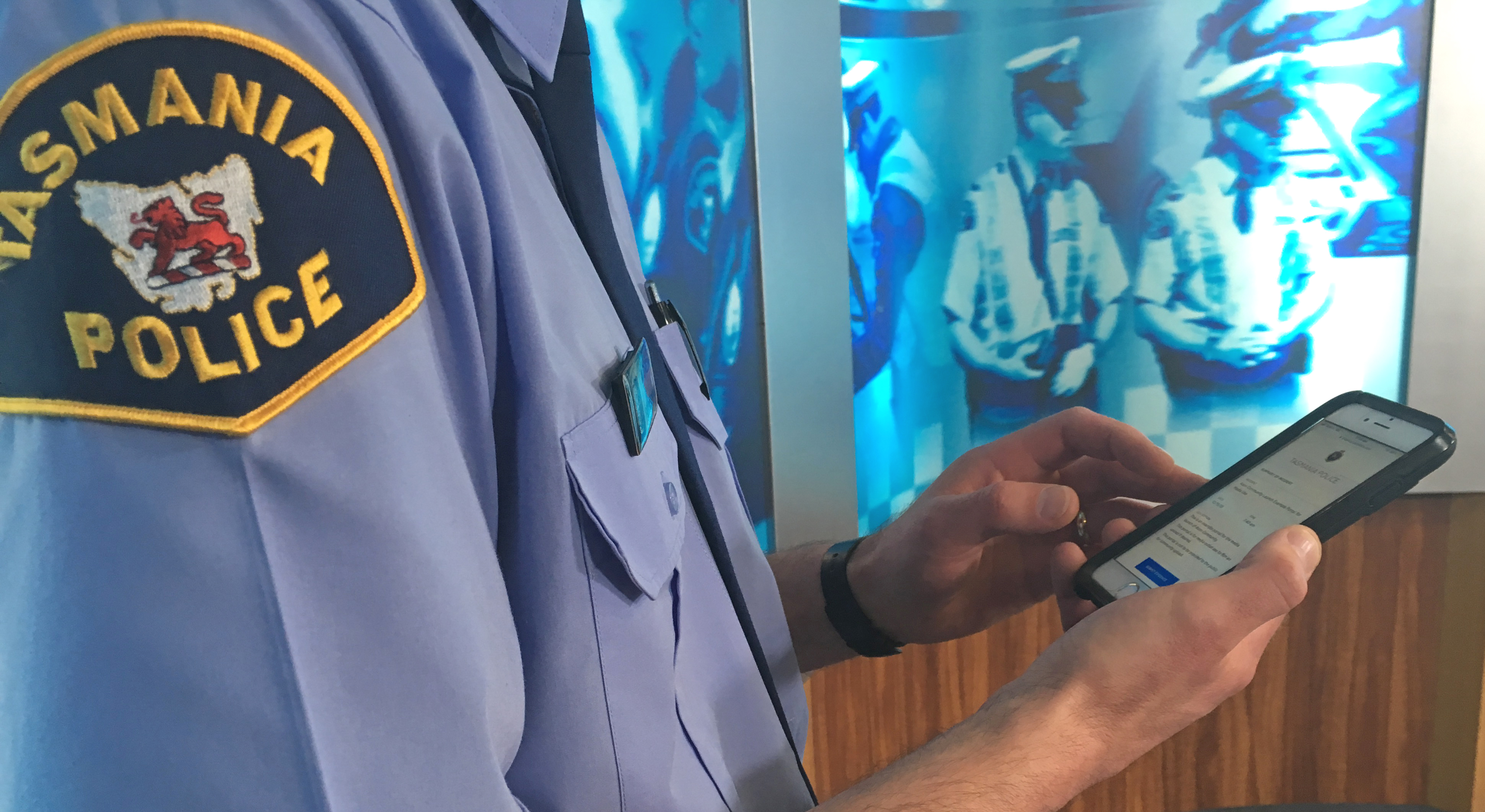 Police officer in uniform accessing Axon Community portal on mobile phone